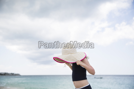side view of girl holding hat