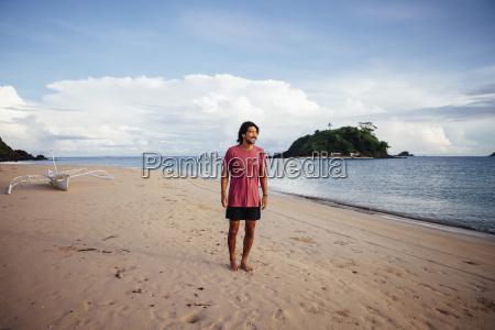 man looking away standing at beach