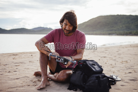 man holding quadcopter while sitting at