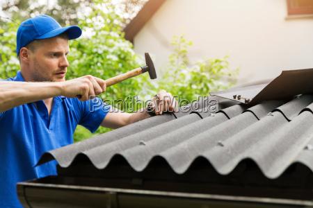 roofer installing bitumen roof sheets