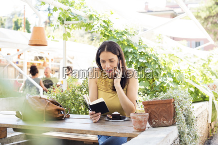 woman reading diary while using smart