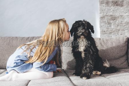 girl kissing dog while kneeling on