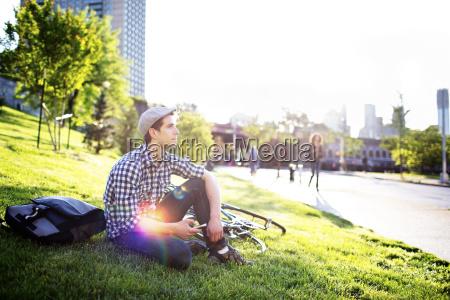 thoughtful man sitting on grass field