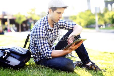 man using digital tablet while sitting