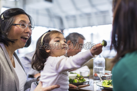 girl feeding mother while sitting with