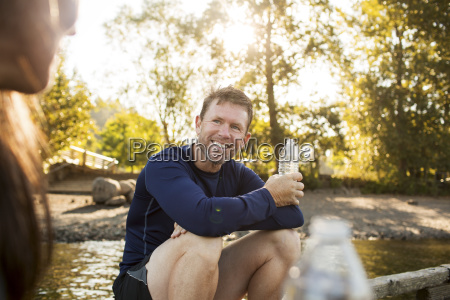 smiling man holding water bottle while