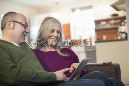 smiling couple using tablet computer while