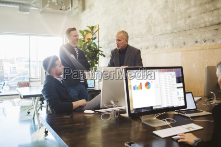 businessmen discussing while female colleague working