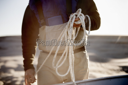 midsection of man holding rope while