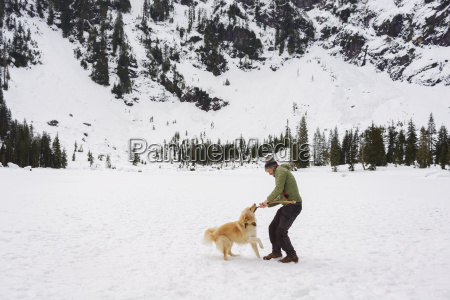 happy man playing with golden retriever