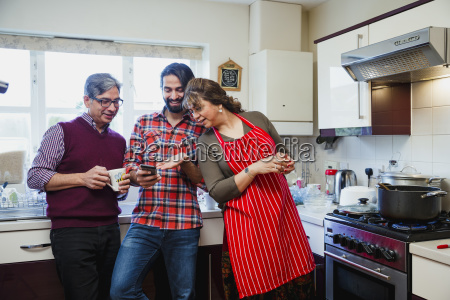 man showing smartphone to parents