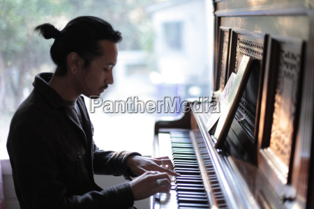 man playing piano against window at
