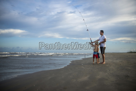 playful father and sons with fishing