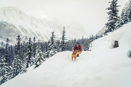 hiker with golden retriever playing on