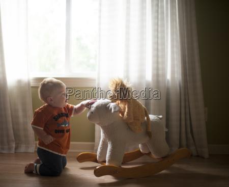 baby boy playing with lamb rocker
