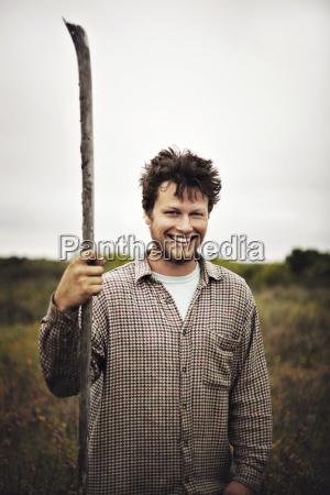 portrait of smiling man holding stick