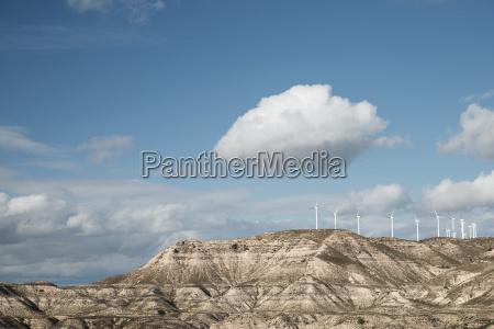wind turbines on mountains against sky
