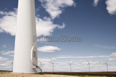 wind turbines on field against blue
