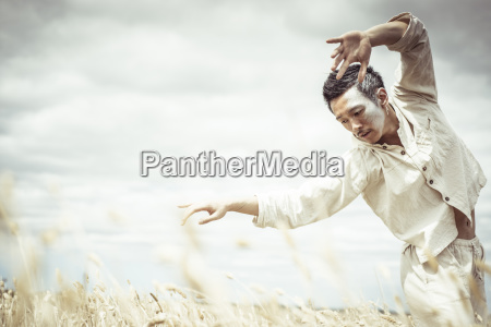 man dancing on field against cloudy
