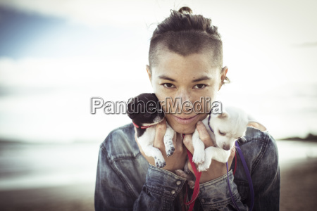 portrait of woman holding puppies while