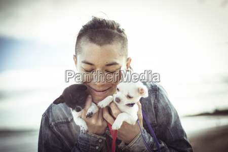 smiling woman holding puppies while standing