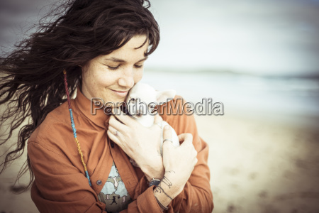 woman holding puppy while standing at