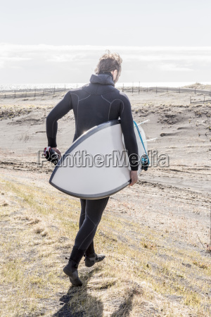 rear view of man with surfboard