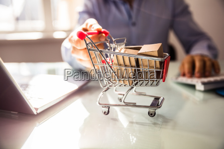 businesspersons hand holding shopping cart