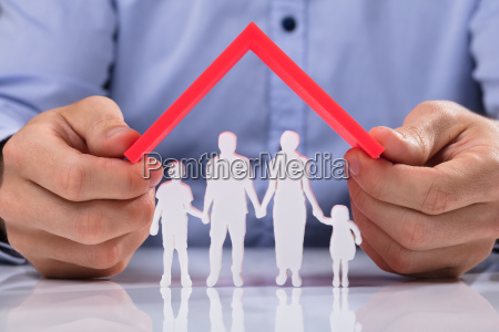 person holding roof over family paper