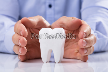 mans hand protecting white tooth