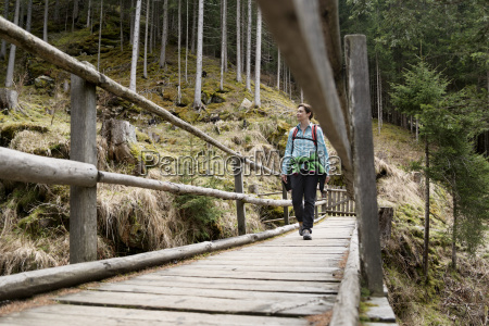 female hiker walking on boardwalk in