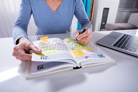 woman writing schedule in calendar diary