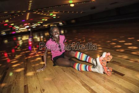 happy woman wearing roller skates sitting