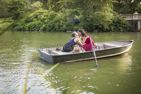 lesbian couple kissing while sitting in