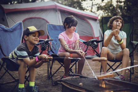 siblings barbecuing in forest