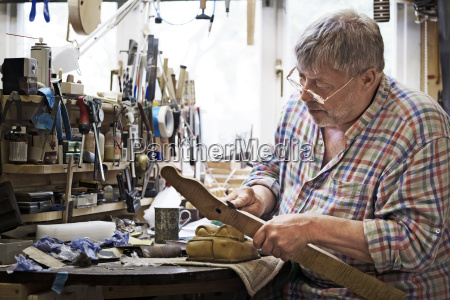 craftsman shaping fretboard in workshop