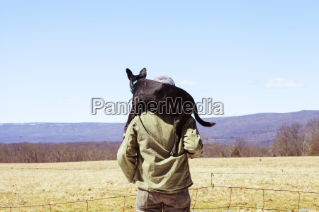 rear view of man carrying dog