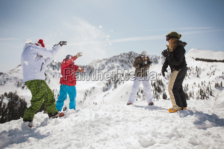 happy skiers playing with snow while