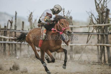 jockey riding racehorse during horse racing