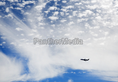 passenger plane flying across cloudy sky