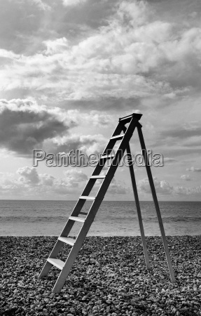 ladder standing on pebble beach by