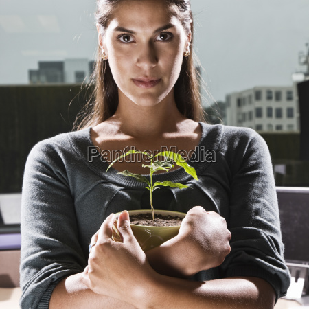 hispanic woman holding a house plant