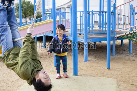 smiling boy looking at father swinging
