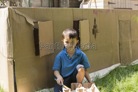 portrait of boy painting against cardboard