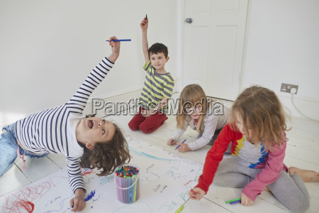 playful children drawing on paper while
