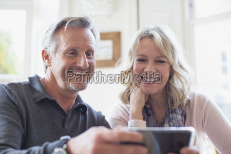 smiling mature couple using smart phone