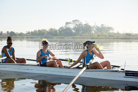 female rowing team resting drinking water