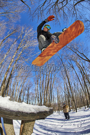 snowboarder in mid air over wooden