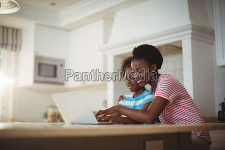 mother and daughter using laptop in