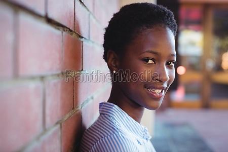 portrait of happy schoolgirl sitting against